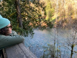 A student at the side of the photo rests their head on a wooden railing in the forest and stares out to the river