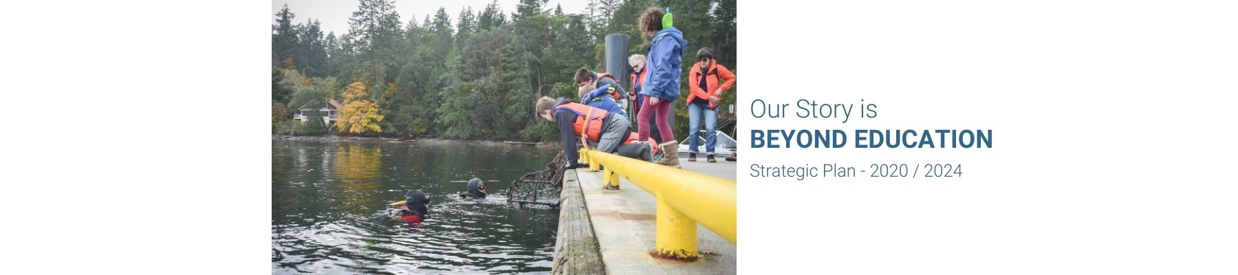 a group of stuents look over a dock to some scuba divers who are brining up items from below