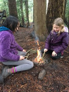 Two young students sit by a campfire